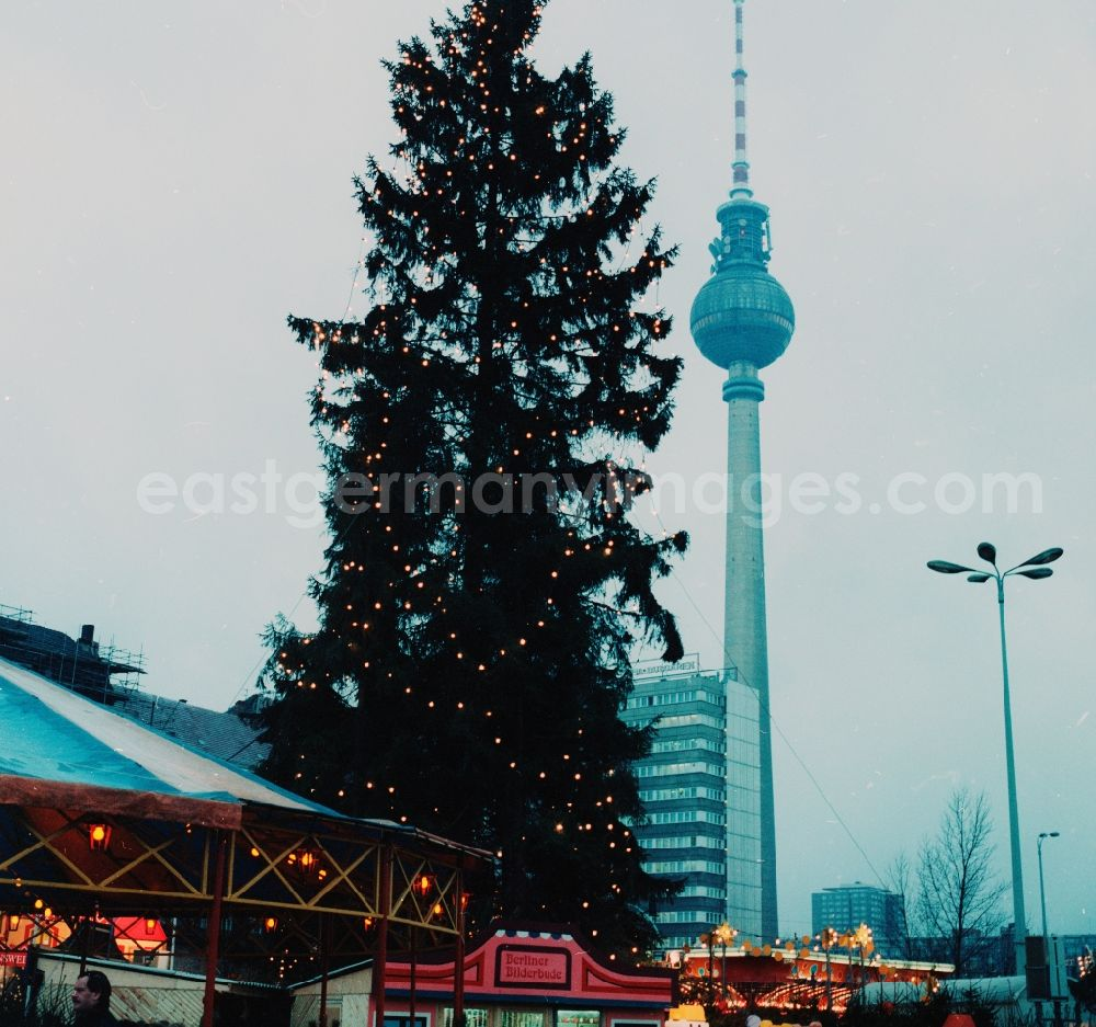 GDR image archive: Berlin - Large Christmas tree on the Christmas market at Alexanderplatz in Berlin, the former capital of the GDR, German Democratic Republic. In the background the Berlin television tower