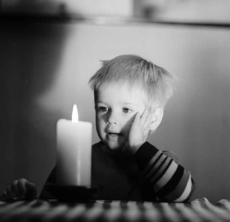 A small child marvels at a burning candle standing on a table in Berlin, the former capital of the GDR, German Democratic Republic.