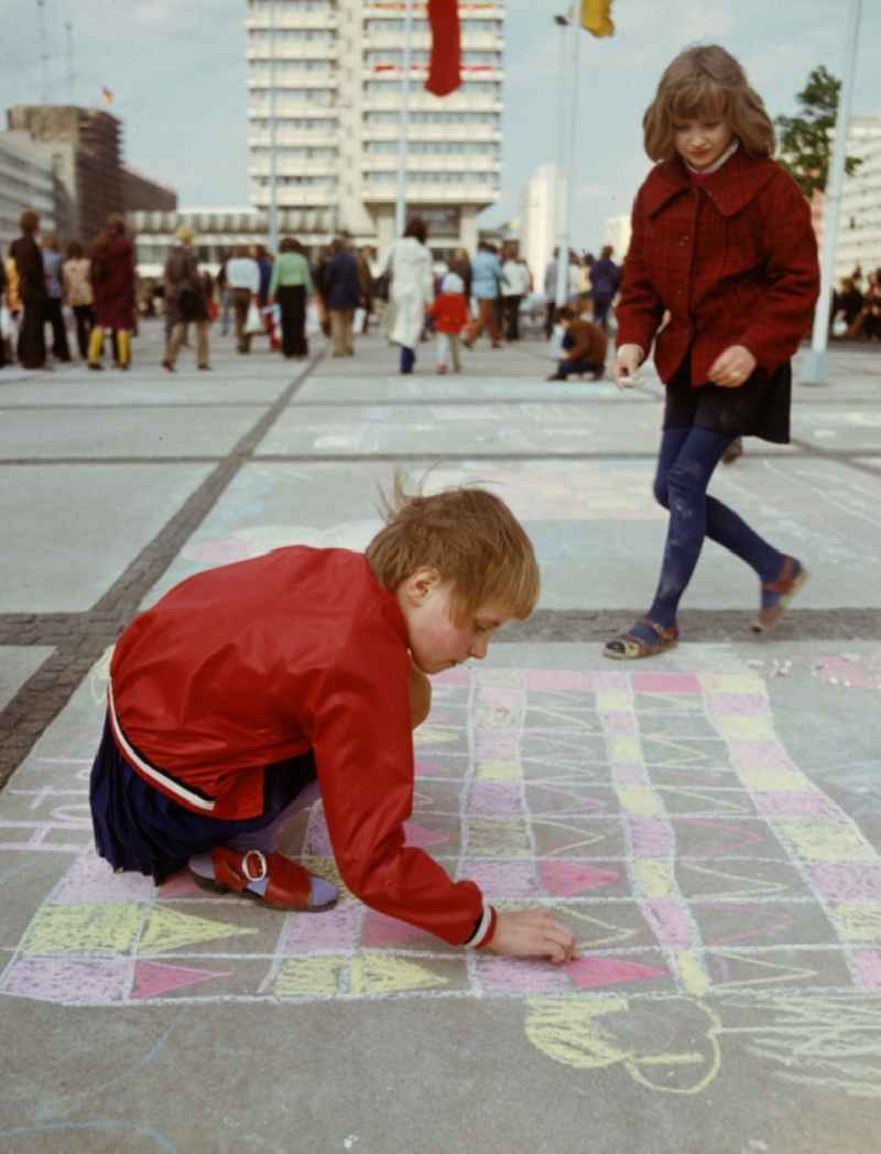 Two girls paint with chalk at the drawing competition for children on the occasion of the traditional celebrations on 1 May at Alexanderplatz in Berlin Mitte, the former capital of the GDR, German Democratic Republic
