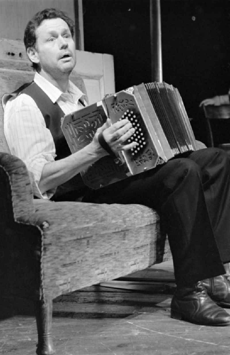 German Theatre Berlin - Berlin Songs From Then And Yesterday. Actors and performers in a theatre - scene and stage set in the Mitte district of Berlin, the former capital of the GDR, German Democratic Republic. On stage - Reimar Johannes Baur with accordion on the sofa