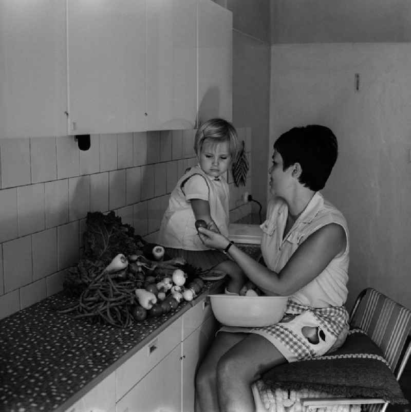A mother sits with her child in the kitchen and dressing vegetables in Berlin - Friedrichshain