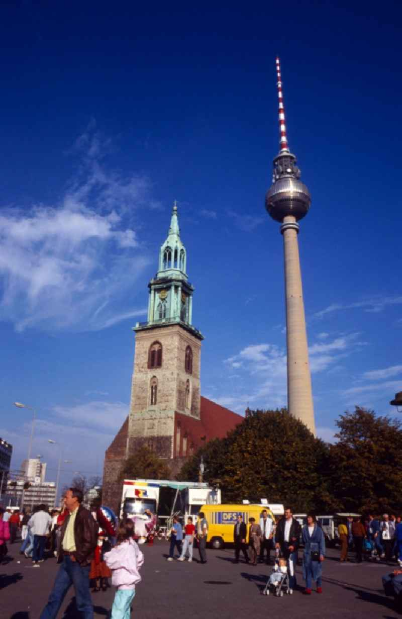 View of the TV tower with the Protestant Marienkirche in Berlin - Mitte. The Berlin TV Tower is the tallest building in Germany. As a politically simplistic ahmtes symbol of the GDR, the distinctive and influential city building has undergone a transition to the citywide icon in reunited Berlin
