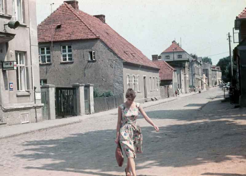 A young woman crosses Schlossstrasse with the Landambulatorium in Neustrelitz in the federal state Mecklenburg-West Pomerania in the area of the former GDR, German democratic republic